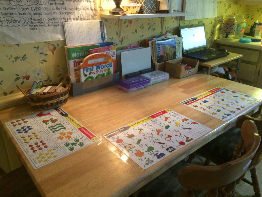 kitchen table with learning placements and activity bins