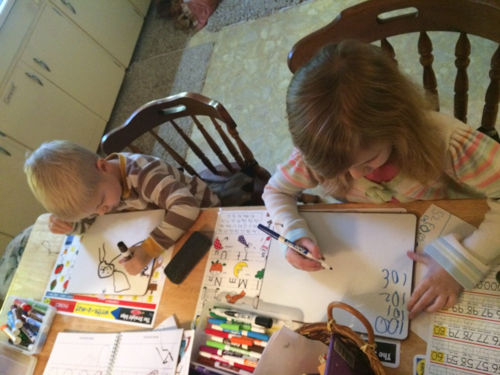 kids using dry erase boards at the kitchen table