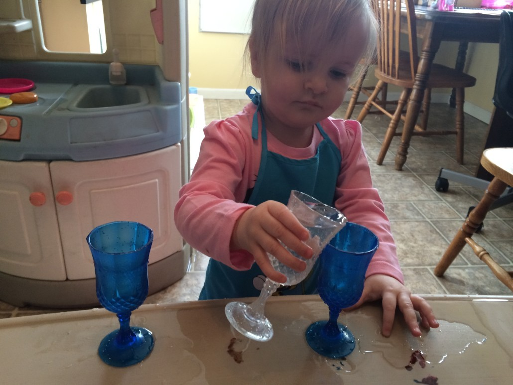 toddler pouring water using little fancy cups