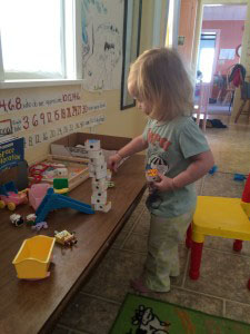 toddler stacking at a coffee table learning station
