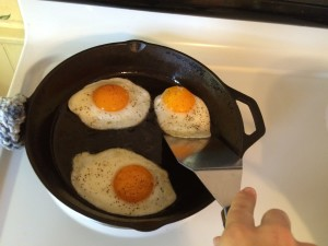three sunny side up eggs being flipped in a cast iron skillet