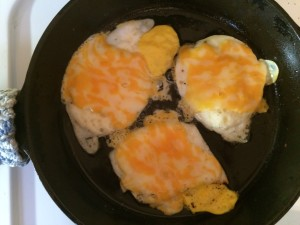 cooked fried eggs with melted cheese in a cast iron skillet